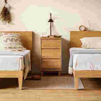 ベッドの間にテーブルを置くことで、2台のベッドが緩やかに繋がり、統一感のある寝室インテリアに。ベッドそれぞれにサイドテーブルを用意するよりも省スペースに。