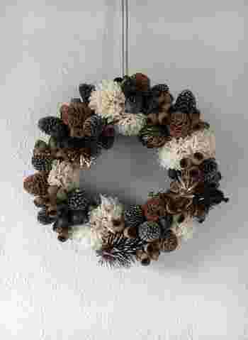 たくさんの木の実とオフホワイトのソラフラワーがぎゅっと集まったリースです。よく見るとネイビーやゴールドの実も混ざっていて、リボンをかければクリスマスリースとしても使えそう。