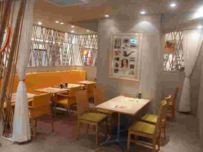 店内は、オレンジのソファが印象的な、明るい雰囲気。木のテーブルが置かれていて、温かい印象を受けます。木の格子でデザインされた壁がおしゃれです。