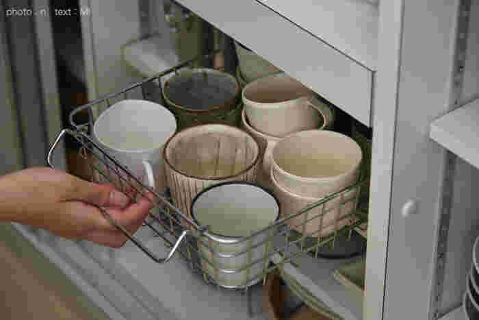 こちらではワイヤーバスケットにマグカップをまとめて収納しています。持ち手があるので食器棚から出す時も楽チン。奥に入れているものも取り出しやすくなります。