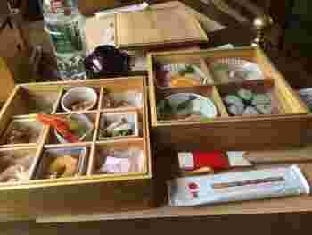 食事は1日4便のうち、朝松山を出発する「大洲編」ではモーニングプレートを、昼の「双海編」「八幡浜編」では食事、夕方の「道後編」ではアフタヌーンティーが提供されます。いずれも2ヶ月ごとにメニューを変更。地元食材を始めとする旬を満喫する品々が楽しめます。  写真は「双海編」の一例。県内産の内子杉の木箱に納められた料理たちが旅の気分を盛り上げます。