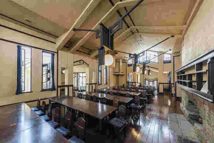 ベージュの壁面にダークブラウンがリズミカルなアクセントを添えている食堂。天井から吊るされた装飾的な照明が印象的です。