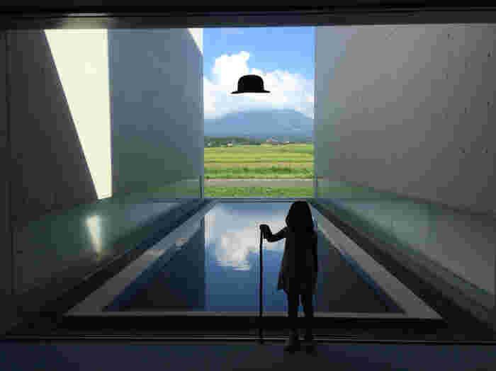 """アート好きならずとも楽しめるのが、こちら。  窓の一部に、植田正治氏の写真でお馴染みの黒い帽子が描かれおり、アングルを工夫してカメラを向けると・・大山が帽子をかぶったように見えるのです。  水面に映る""""逆さ大山""""を楽しめることでも有名。アートや大自然とともに、思考を凝らした建築デザインの美しさにも浸る、癒しの時間を過ごせる場所です。"""