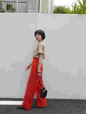 鮮やかなオレンジのハイウエストパンツ。股上が深めのデザインは、お腹まわりをカバーしながら、すらっと脚長に見せる効果も期待できます。丈の長いボトムスにヒールを合わせれば、一気にモードな印象に。