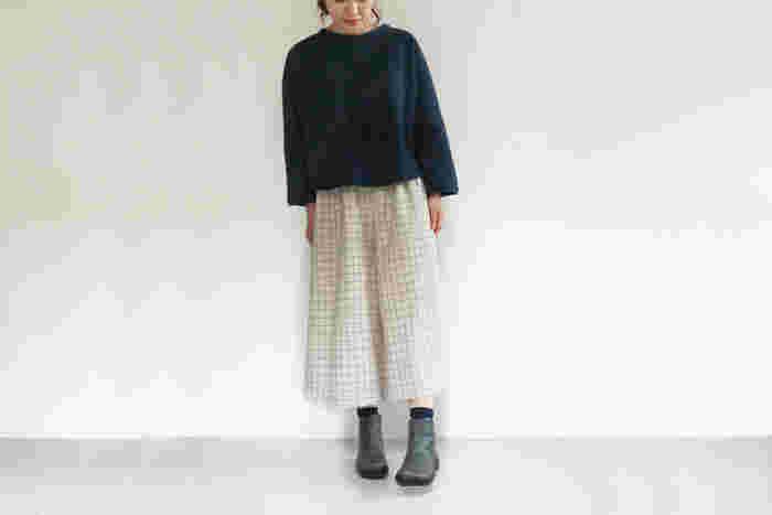 こちらのコーディネートは、トラディショナルなチェック柄のボトムスと、モダンなデザインのショートブーツ「SCALLOP(スカラップ)」の組合せが新鮮な印象です。やわらかいトーンのグレーのショートブーツは、シンプルな着こなしに女性らしさと上品さをプラスしてくれます。