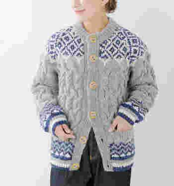 肉厚のウール100%の毛糸を使用し、ざっくりと編み上げたノルディックニット柄のカーディガン。大きめのボタンがキュートな印象で、前を留めてトップス風にしても、羽織りとしても活用できます。
