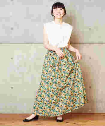 ヒマワリを並べたプリントスカートに、白のノースリーブトップスを合わせたコーディネートです。インパクト抜群の総花柄スカートに、白トップスをタックイン。スカートを主役にした、華やかコーディネートに仕上げています。
