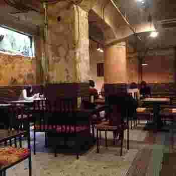 その昔、進駐軍のダンスホールとBARだったといわれる空間。御幸町通りの足下に開けられてた明かり取りの窓から光が差しますが、廃墟を思わせるような退廃的なムードの店内はなんだか別世界。モザイクタイルの床、手作業で造られた鉄細工の椅子やテーブルが独特の雰囲気を醸し出しています。3階に劇場、1階にギャラリーがあることも影響してなのかアーティスティックなお客さんが多いようです。