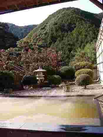 露天風呂からは美しく整えられた庭園と共に、山あいの景色も楽しめます。 お湯が茶褐色なのは鉄分を多く含んでいるため。疲労回復に効果があるんだそう。