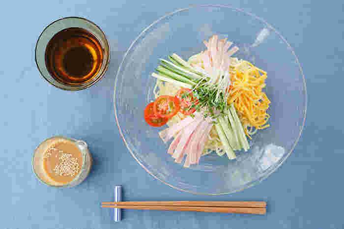 夏の風物詩、冷やし中華を涼しげに盛り付けたテーブルコーディネート。使用している沖縄の<ガラス工房 晴天>の気泡皿(大)は、再生ガラスを使った琉球ガラスの製法にこだわって作られています。ふつふつと気泡が混さった、緑がかった色合いがとても爽やかですね。冷しゃぶサラダ、カッペリーニなど、夏のご馳走にぴったりなお皿です。