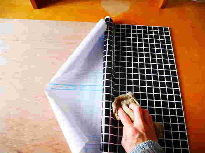 リメイクシートをマスキングテープで仮止め。ゆっくりと後ろの紙を剥がして、貼り付けていきます。カッターで余分な部分のシートをカットすれば完成です。