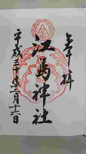 御朱印は、北条家の家紋「三枚の鱗」の伝説にちなみ「向い波の中の三つの鱗」を表現しています。その昔、北条時政が子孫繁栄を願うため現在の岩屋に参籠したところ、弁財天が現れ願いを叶えるたことを約束し、大蛇の姿となり海に消え、あとに残された三枚の鱗を時政が家紋にしたと伝えられています。