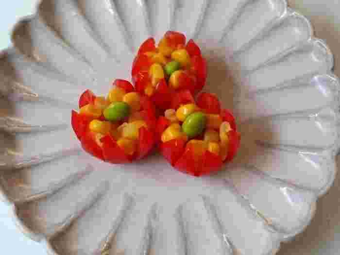 【ミニトマトの飾り切り】 トマトのおしり側に交差するように4本切り込みを入れ、スプーンで中身を取り出し、コーンや枝豆を詰めれば完成です!