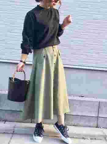 前ボタンや変形ポケットがキュートなフレアスカートはブラックのトップスと小物を合わせてクールにきこなしたい。