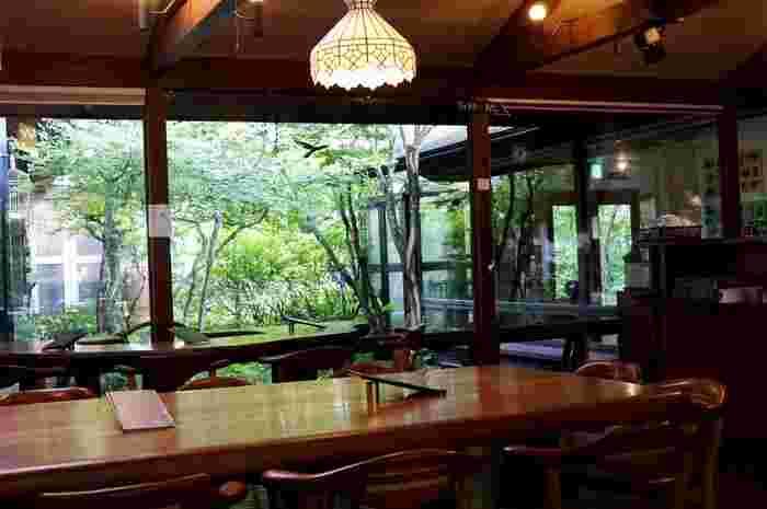 赤い柱がキュートなカフェレストランは、木を基調に作られた温かい雰囲気。屋内からも、雑木林が織りなす四季折々の景色が楽しめます。