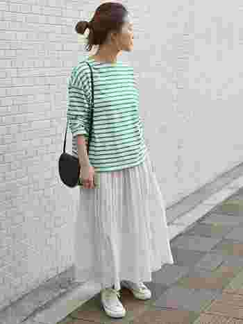 若葉を思わせる爽やかなグリーンのボーダーは、ギャザーたっぷりのスカートと合わせてナチュラルな雰囲気に。足元はスニーカーを合わせて甘くなりすぎないように見せています。