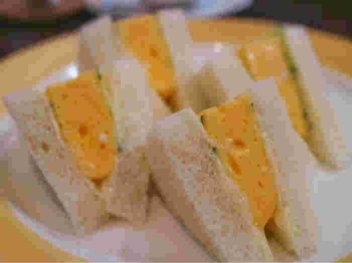 ビジュアルから思わず惹かれる「焼きたまごサンド」は、お腹をやさしく満たしてくれる1品。  ふんわりとあまく厚いたまご焼きを、きゅうりと一緒にやわらかなパンで挟んであります。