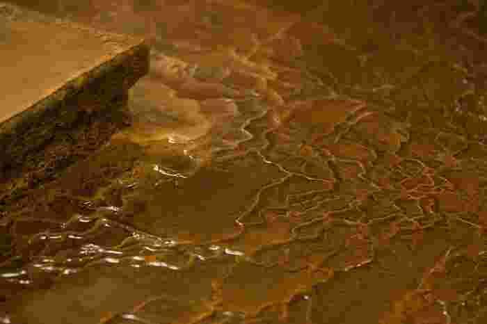 """温泉は、ミネラル豊富な天然の湧き水や地下水、化石海水に、火山起源によるエネルギーが加わったものです。  地下でプレートが重なり合う日本列島は、世界有数の火山大国です。常に動くプレートは、沈み込む際のエネルギーによってマグマを生じ、周辺の岩石や湧水、地下水を温めます。日本は、噴火災害のリスクを負ってはいるものの、""""温泉""""という大きな恩恵を自然から得ています。  清らかな水に浄化作用があり、水の湧き出る場所が神聖な領域とされるのなら、古くから大事にされてきた""""温泉""""には、きっと偉大な力が具わっているはずです。そして、その温泉が""""源泉かけ流し""""であるならば、温泉のパワーが薄まることなく享受できるはずです。"""
