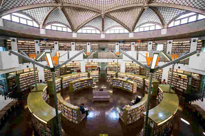 中央が吹き抜けで2階の壁面が書架になっています。約10万冊の本が丸く囲むようなつくりは、まるでサン・ピエトロ広場の大回廊を彷彿とさせる空間に。デザイン性の高い図書館ですが、落ち着いた雰囲気が漂っています。2階にはソファーもあるので、気になった本があればゆっくりと読書を楽しみましょう。