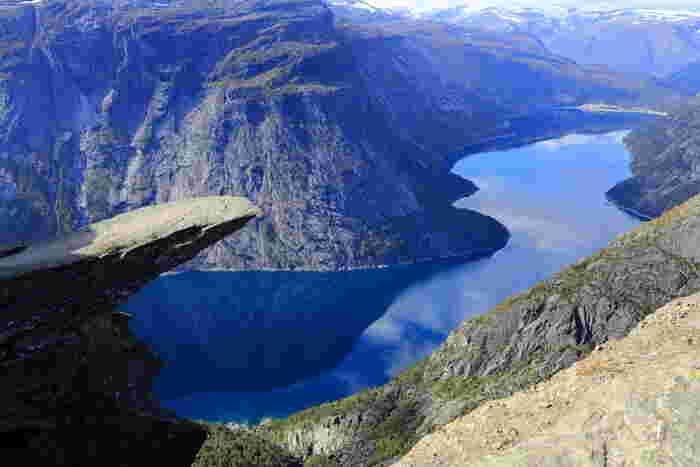 ノルウェー西部のハダンゲルフィヨルドにあるトロルの舌は、フィヨルドに対して水平に突き出た岩板です。トロルの舌からの眺望は格別です。複雑で入り組んだ美しい海岸線を持つフィヨルド、周囲の岩山を鏡のように映し出す水面が融和した景色はまさに絶景そのものです。
