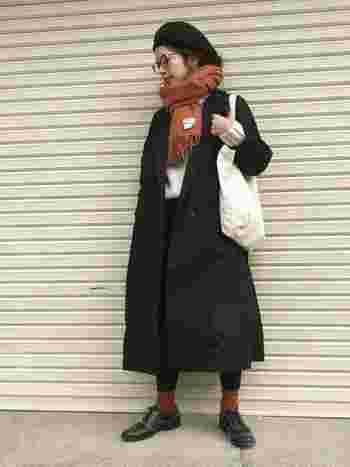 シンプルなブラックのトレンチ。マフラーとソックスの色を合わせてコーデに統一感をプラス。