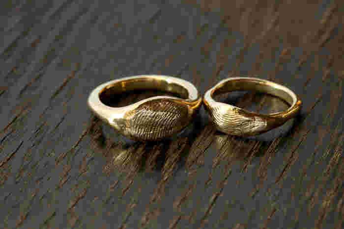 指輪の中央に大きく指紋を捺印したリング。他にも、少し細身のものや石をプラスしたタイプの指紋リングもある