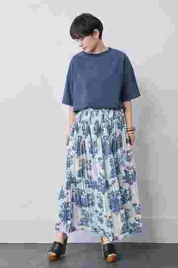 白地に青の花柄を描いたプリーツスカートに、ネイビーの無地トップスをタックインしたコーディネート。同系色で揃えているので、爽やかなスカートスタイルに仕上がっています。足元は黒のサンダルで、ちょっぴり引き締め感をプラス。