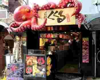 地下鉄御堂筋線の、なんば駅より徒歩約3分の距離にある「道頓堀くくる 本店」。大阪市天王寺区にて1947年に開業した白ハト商店が、1959年に「白ハト食品工業株式会社」に改組し、その後、白ハト印いも菓子専門店や、アイスキャンディーなどの開発を手がけ、1985年にこちらの「道頓堀くくる 本店」の前身である「たこやきハウス「KU/KU/RU道頓堀店」をオープン。