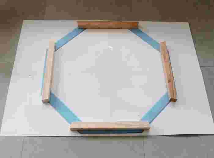 はじめに八角形の模型に合わせて、写真のように一間隔ずつ空けて木材を並べます。次に1段目で間隔を空けた部分に木材をのせて、2段目を作ります。