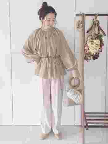 ハイネックのフレアブラウスは、無地でも主役になる存在感です。ボリューミーなシルエットが特徴で、ウエストを絞れば丸みのある可愛いシルエットに。白のパンツで明るいコーデに仕上げると爽やかですね。