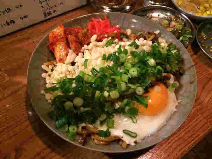こちらは大人気の「西尾の焼きそば」。太麺が隠れるくらいにトッピングした「ねぎ」「天かす」「ショウガ」「目玉焼き」を全部混ぜまぜしていただきます。飲んだ後のシメに是非とも注文したいメニューです。