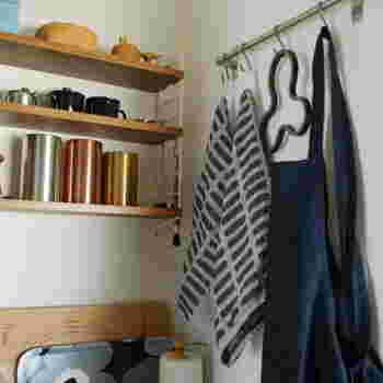 """料理の度に使いたい「エプロン」は、「S字フック」で吊るして収納して。その他にもキッチンクロスや鍋敷き、ミトンなどお気に入りのキッチンアイテムも吊るして""""見せる収納""""に。"""