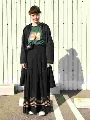 黒のロングコートにボリューミーなマキシ丈スカートにコートを合わせたビッグシルエットコーデ。インナーのTシャツは、ウエストにINしてすっきりと。グリーンの差し色とスカートの裾のラインでアクセントを効かせています。短めに斜めがけしたミニショルダーとのバランスも◎