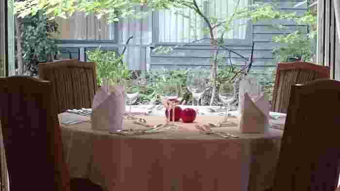 """レストランのコンセプトは""""木立に囲まれた隠れ家""""。大きな窓からは軽井沢の四季折々の景色を眺められます。気軽に楽しんでほしいという想いから、ドレスコードはなし。気負わず訪れやすいのも魅力です。"""
