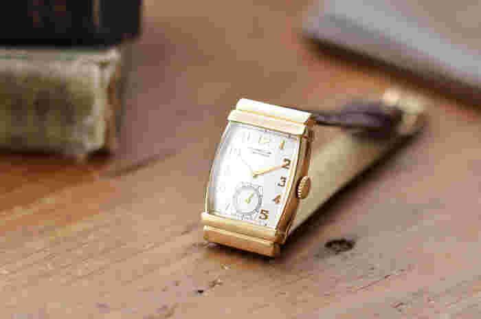 近頃はスマートフォンで時間を確認できるからと、腕時計を身につけない人も多いのだとか。 しかし誰かと一緒にいる時にスマホで時間の確認をするのは美しくないですし、ビジネスシーンではもってのほか。 普段は使わなくても、大切な場面ではきちんと腕時計を身につけたいですね。  こちらは、1940年代のデザインをベースにつくられた、アールデコな雰囲気漂う腕時計。 ゴールドのケースと型押しの上質な本革ベルトの組み合わせが美しく、ハンドセットされたアラビア数字や、6時位置にセットされたスモールセコンドなど、手の込んだ文字盤にこだわりを感じます。