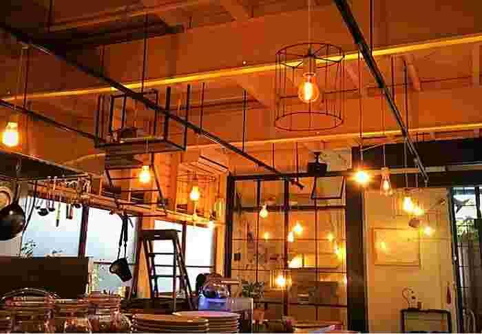 """オープンは2012年。吹抜けにして小屋裏を見せた店内は、ダイソン「ホット&クール」やテーブルに置かれたサボテンなどの演出によって、""""食堂""""というよりカフェの雰囲気。ギャラリースペースとしても利用できます。"""