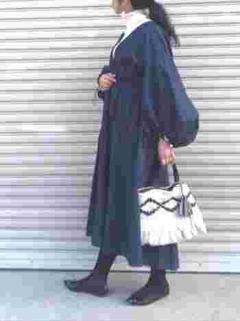 袖にボリュームのあるワンピースに、白のタートルネックをインすればほっこりと優しい雰囲気に。パンプスとタイツには黒をチョイスして、着こなしを引き締めています。