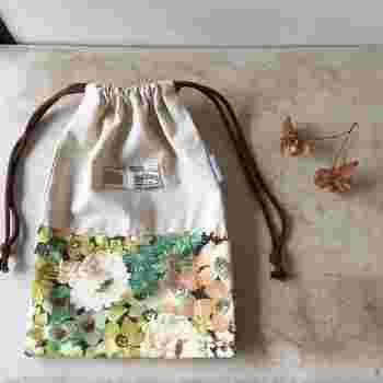 コットンとリネンの布の組み合わせがナチュラルな雰囲気いっぱいの巾着。上級者さんは、さらにタグをバランス良くつけて、一段とおしゃれに!