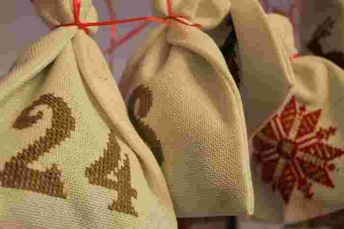 シックな色合いの小さめ巾着を作って日付を刺繍して、紐などでまとめて。巾着なら来年以降も使うことができて便利です♪