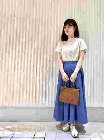 光沢とドレープが美しい、夏らしいブルーのスカートは一枚で主役級のアイテム。トップスもサンダルも相性がいい白でまとめて爽やかに。