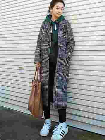 チェック柄のチェスターコートにグリーンのパーカーを合わせたスタイリング。秋冬らしい色柄で、シンプルコーデにシックな彩りを添えて。