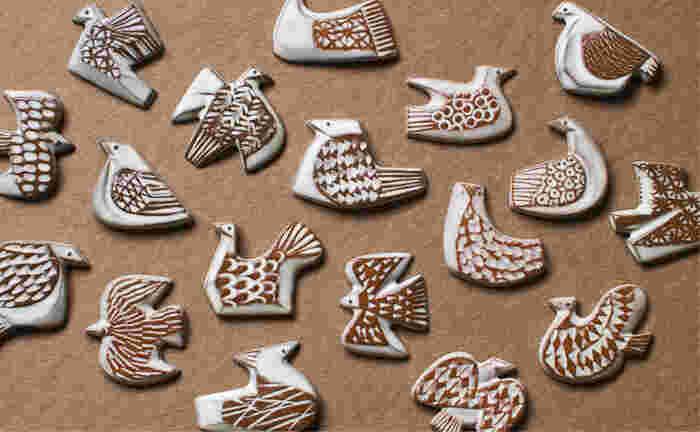BIRDS' WORDS(バーズワーズ)は、デザインディレクターの富岡正直さんと陶芸作家の伊藤利江さんが手掛けるブランド。 鳥や花などの自然をモチーフにした、思わず手に取りたくなるアイテムの数々は、忙しい日々の中で、どこか心があたたまる気持ちにさせてくれます。 こちらは、それぞれに違った模様が施された18種類の鳥のブローチ。模様が浮き出るように作られたデザインで、ひとつづつ手作業で仕上げてあるため、形や釉薬の表情がひとつづつ異なります。
