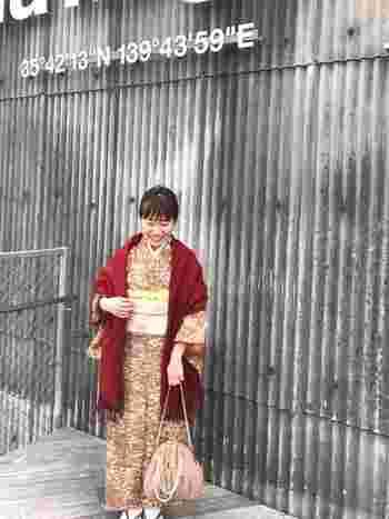暖色の着物にボルドーのストールを羽織って。パール付きのがま口のバッグを合わせて、今っぽさも取り入れて可愛らしく仕上げています。