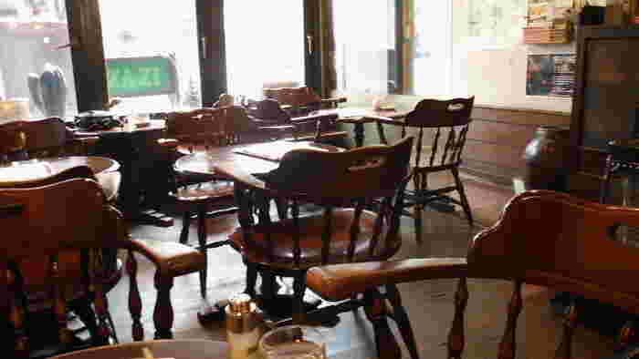 磨き込まれたレトロなテーブルや椅子が落ち着ける雰囲気。通りに面した1階席と、2階にも席があります。ドリンクやケーキなどでお茶に寄っても落ち着けますよ。