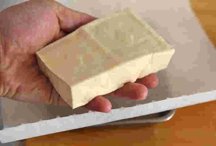 スタンダードな重しをのせるやり方は、最もしっかり水切りできる方法です。キッチンペーパーを2~3重にして豆腐を包み、豆腐と同じか倍くらいの重さの重しをのせ、冷蔵庫に入れておきます。時間は料理によって変わりますが、基本的な水切り方法は同じ。覚えておきたいやり方です。