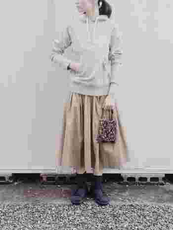 女性らしさの象徴のスカート、カジュアルでスポーティーな印象のパーカー。テイストの異なる2つのアイテムを同時に取り入れることでどんなことが起こるんだろう???