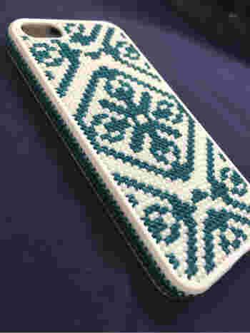 落ち着いたブルーグリーンでまとめられたノルディック模様のスマホカバー。サイド部分までラインを施して丁寧な作りになっています。