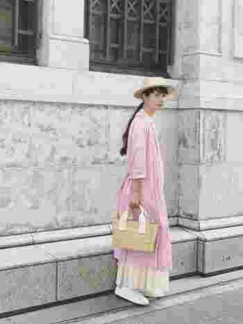 さくらピンクのワンピースにホワイトのスカートを忍ばせれば、トレンド感のある重ね着スタイルが完成。かごバッグで季節感もバッチリです。