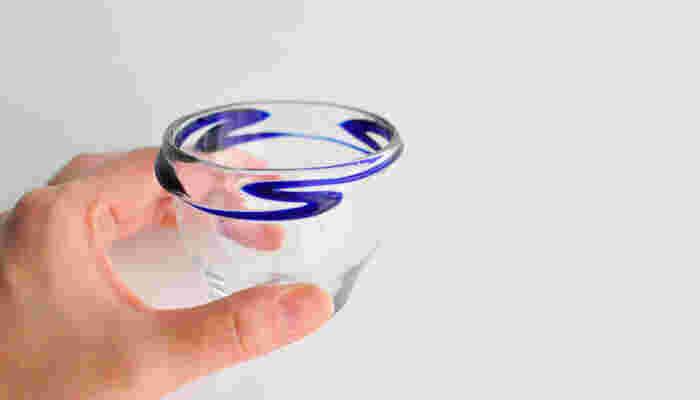 お酒の色を楽しめるクリアな琉球ガラスに、青い波のデザインがアクセントになったぐい呑み。やちむんの里で活動する「小野田郁子」さんの作品です。夏は、冷酒もいいですね。