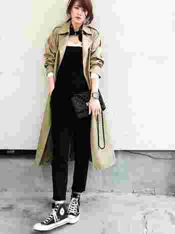 黒のサロペットにロングトレンチコートを羽織って、縦ラインを強調したシックで秋らしい大人のコーディネートです。